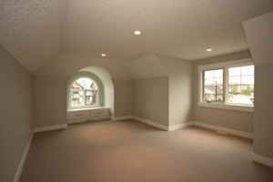 An upstairs bonus room with carpet flooring